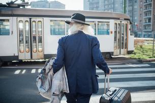 Senior businessman with wheeled luggage walking on pedestrian crossing, Milano, Lombardia, Italyの写真素材 [FYI03621337]