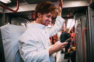 Astronaut using smartphone in trainの写真素材 [FYI03621360]