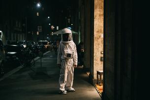 Astronaut walking on pavement at nightの写真素材 [FYI03621375]