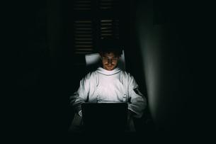 Astronaut using laptop in dark roomの写真素材 [FYI03621384]