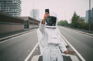 Astronaut taking selfie in middle of roadの写真素材 [FYI03621385]