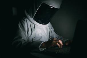 Astronaut using laptop in dark roomの写真素材 [FYI03621390]