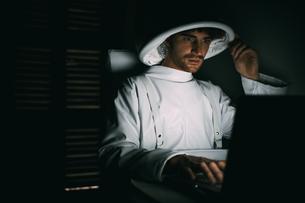 Astronaut using laptop in dark roomの写真素材 [FYI03621391]