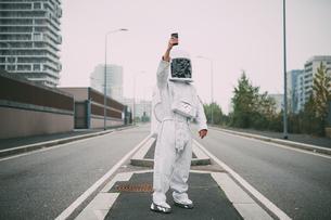 Astronaut taking selfie in middle of roadの写真素材 [FYI03621393]