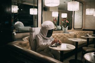 Astronaut having coffee in restaurantの写真素材 [FYI03621400]