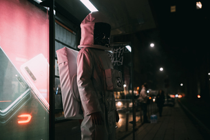 Astronaut standing at illuminated bus stopの写真素材 [FYI03621403]
