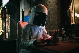 Astronaut using smartphone at sidewalk cafeの写真素材 [FYI03621407]