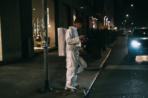 Astronaut using smartphone on pavementの写真素材 [FYI03621408]