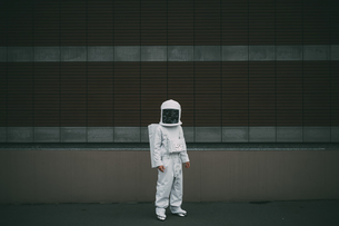 Astronaut standing against striped concrete wallの写真素材 [FYI03621409]