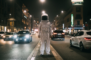 Astronaut in middle of busy street at nightの写真素材 [FYI03621411]