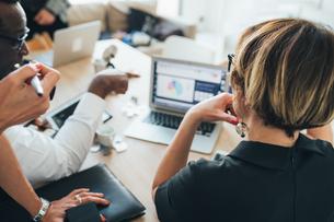 Businessmen and businesswomen having discussion in loft officeの写真素材 [FYI03621443]
