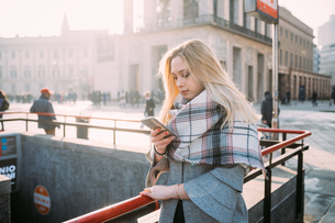 Young woman looking at smartphone by underground station, Milan, Italyの写真素材 [FYI03621518]