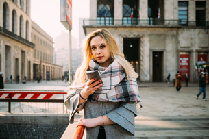 Young woman with smartphone by underground station, portrait, Milan, Italyの写真素材 [FYI03621519]
