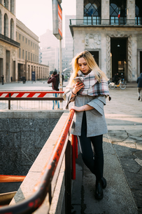 Young woman by underground station looking at smartphone, Milan, Italyの写真素材 [FYI03621524]