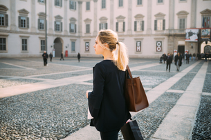 Young female tourist with shopping bags in city square, Milan, Italyの写真素材 [FYI03621532]