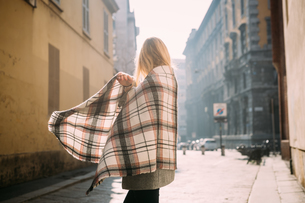 Young female tourist wrapping herself in shawl, side view, Milan, Italyの写真素材 [FYI03621547]