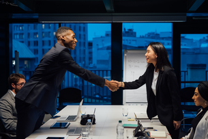 Businesswoman and male client shaking hands over conference table meetingの写真素材 [FYI03621578]