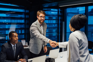 Businessman and female client shaking hands over conference table meetingの写真素材 [FYI03621580]