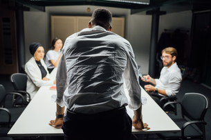 Businessman in front of team at conference table meeting, rear viewの写真素材 [FYI03621637]