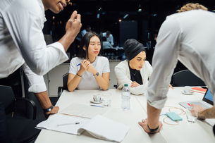 Businessmen and women having discussion over conference table meetingの写真素材 [FYI03621643]