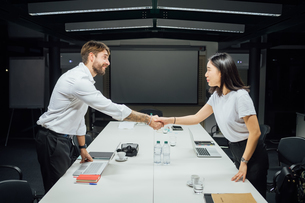 Businesswoman and man shaking hands over conference tableの写真素材 [FYI03621653]