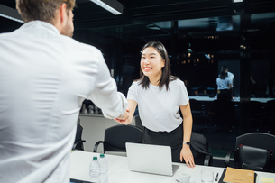 Businessman and woman shaking hands over conference tableの写真素材 [FYI03621654]