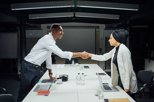 Businessman and woman shaking hands over conference tableの写真素材 [FYI03621655]