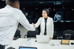 Businesswoman and man shaking hands over conference tableの写真素材 [FYI03621656]
