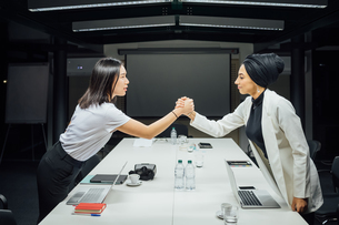 Businesswomen shaking hands over conference tableの写真素材 [FYI03621660]
