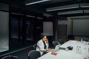 Businesswoman at conference table typing on laptopの写真素材 [FYI03621661]