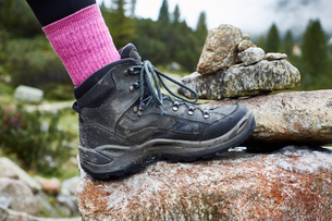 Female hiker stepping onto rock, close up of hiking bootの写真素材 [FYI03621689]