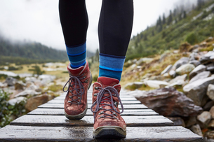 Female hiker hiking across wooden footbridge, cropped view of legs and hiking bootsの写真素材 [FYI03621690]