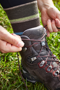 Female hiker fastening hiking boot laces, close upの写真素材 [FYI03621694]