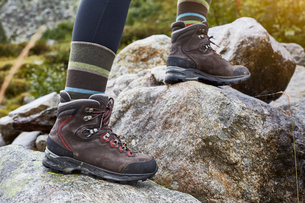 Female hiker stepping over rocks, cropped view of ankles and hiking bootsの写真素材 [FYI03621706]