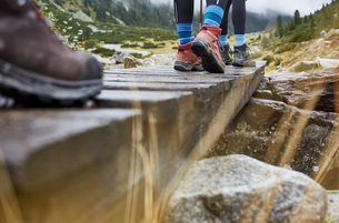 Female hikers hiking across wooden footbridge, cropped view of legs and hiking bootsの写真素材 [FYI03621707]