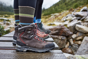 Female hikers standing on wooden footbridge, cropped view of ankles and hiking bootsの写真素材 [FYI03621711]