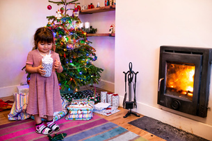 Girl standing next to living room christmas tree looking at christmas presentの写真素材 [FYI03621734]