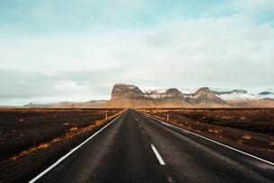Road leading towards mountain ranges, K疝fafell, Vestur-Skaftafellssysla, Icelandの写真素材 [FYI03621768]