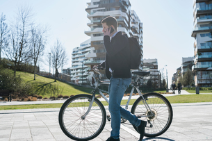 Man pushing bicycle and using smartphone, passing multi-storey building, Milan, Lombardia, Italyの写真素材 [FYI03621910]