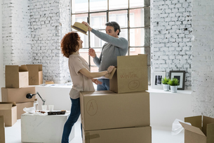 Couple moving into industrial style apartment, unpacking straw hat from cardboard boxの写真素材 [FYI03621928]