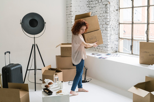 Mid adult woman moving into industrial style apartment, carrying boxesの写真素材 [FYI03621931]