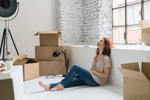 Mid adult woman sitting on floor relaxing, moving into industrial style apartmentの写真素材 [FYI03621932]
