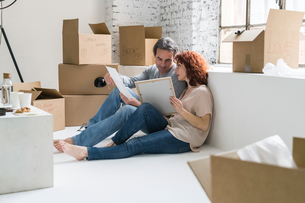 Couple moving into industrial style apartment, sitting on floor  looking at picturesの写真素材 [FYI03621935]