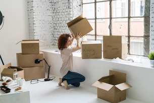Mid adult woman moving into industrial style apartment, stacking boxesの写真素材 [FYI03621938]