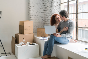 Romantic couple moving into industrial style apartment, sitting on window ledge with laptopの写真素材 [FYI03621949]