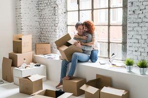 Romantic couple moving into industrial style apartment, sitting on window ledge huggingの写真素材 [FYI03621956]