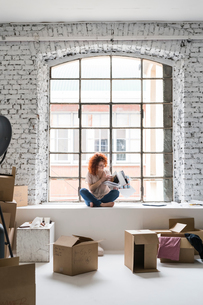 Mid adult woman moving into industrial style apartment, sitting on window ledge looking at magazineの写真素材 [FYI03621960]