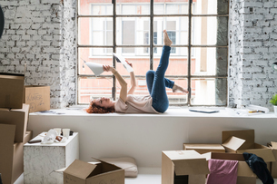 Mid adult woman moving into industrial style apartment, lying on window ledge looking at photographsの写真素材 [FYI03621961]