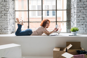 Mid adult woman moving into industrial style apartment, lying on window ledge looking at photographの写真素材 [FYI03621966]