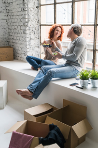 Couple moving into industrial style apartment, sitting on window ledge eating takeaway mealの写真素材 [FYI03621972]